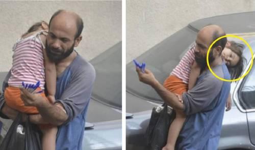 Soportando las incomodidades de la calle este hombre con su pequeña niña dea..