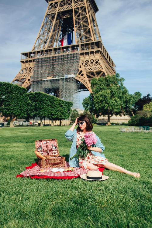 Mujer sentada en la grama con una cesta y mantel lista par un picnic con la torre Eiffel de fondo