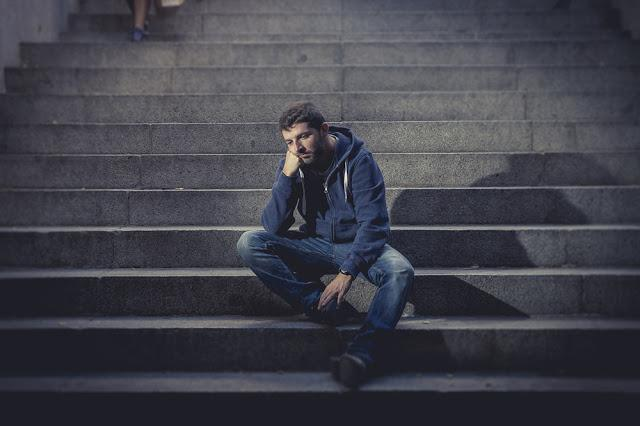 Young desperate man in casual clothes abandoned lost in depression sitting on ground street concrete stairs alone suffering emotional pain, sadness, looking sick in grunge lighting