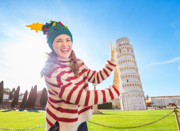 Mujer con gorro de navidad sosteniendo la Torre de Pisa